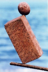 Stone and brick balanced on rod